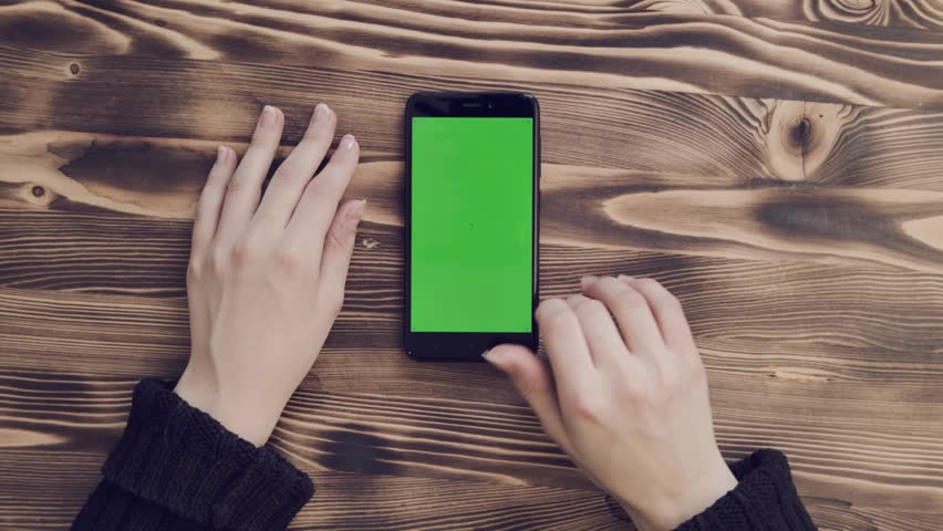 Smartphone with green screen lies vertically on wooden table. Hands of young girl work using mobile. Finger on right on left scrolls menu of mobile application. Hands of girl and smartphone closeup	 #1008531634