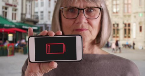 Senior female holding phone up to camera with low-battery indicator flashing. Casual woman with phone with low-battery warning flashing on screen to camera in city street. 4k