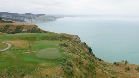 Aerial shot of golf hole on a cliffside golf course with blue sea in the distance.