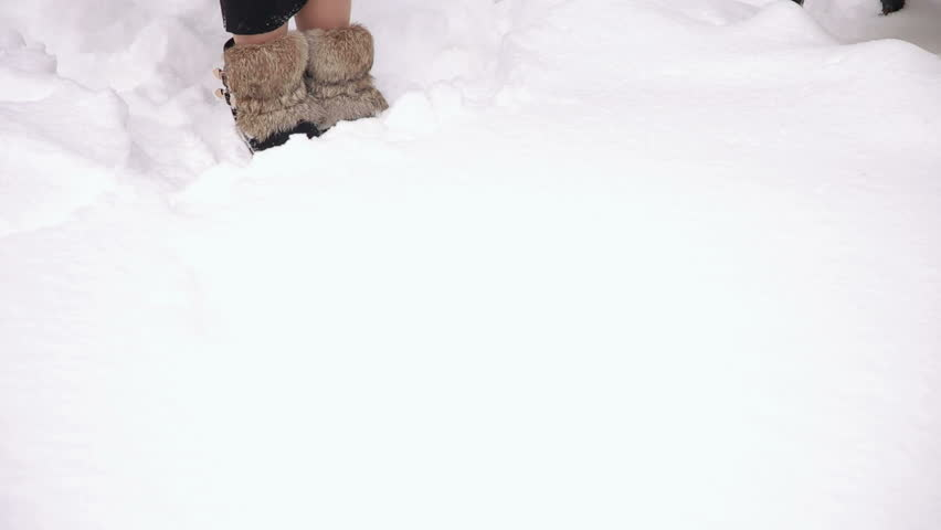 Close-up of a girl in a black long dress and fur boots walks through deep snow in the park. | Shutterstock HD Video #1008561514
