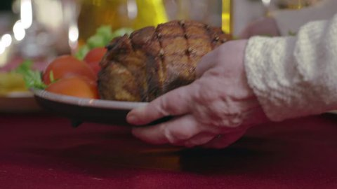 Close-up of an elderly woman's hand, which puts freshly prepared meat on the table, a plate on the table, a gala dinner