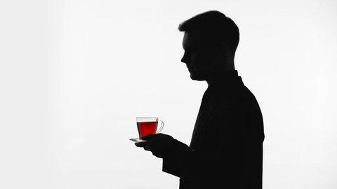 Dark silhouette of man drinking glass of tea, recreation, pH balance restore