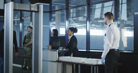 Airport security agent using a metal detector on a male passenger in a suit to pat him down at the boarding gate after passing through the x-ray scanner. 4K shot on Red cinema camera.