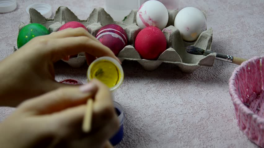 easter, family, holiday and child concept - close up of little boy coloring eggs for easter.