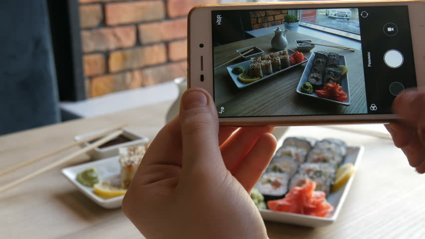 Hands of a teenager make a photo of food on a smartphone. A set of sushi rolls from Japanese cuisine on the background of a porcelain teapot for soy sauce and saucer in a stylish cafe