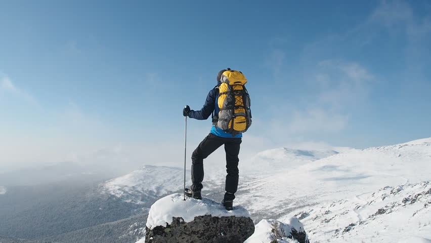 Young Hiker Man Standing On Top Of The Mountain. Mountain Alps Mountaineering Snow Climbers Travel. Man Raising Hands On Mountain Top Winner Concept. Man Enjoying Freedom And Happiness During Hike.