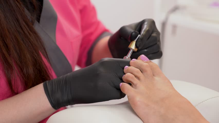 Cuticle massage with cuticle oil in beauty salon. Closeup of woman feets. Spa treatment.