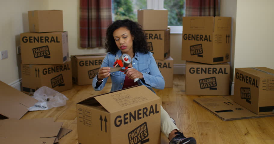4K Depressed woman evicted from her home packing boxes for moving out. Slow motion.