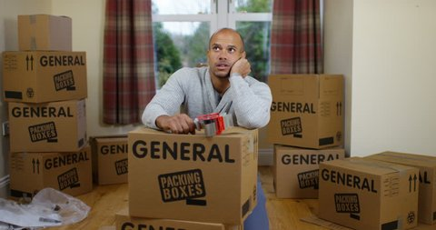 4K Fed up man packing boxes for house move, looking at camera with sad expression. Slow motion.