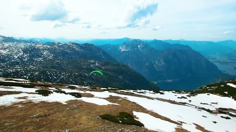 Aerial panoramic view of a flying paraglider of green color parachute from the snowy mountains in Austria. Beautiful views in the Alps