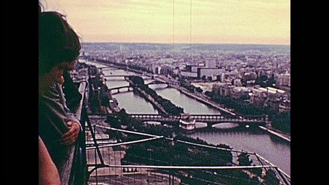 PARIS, FRANCE - CIRCA 1976: Tourists in observation view of vintage Eiffel Tower. Paris aerial view of Senna river with bridges. Historic archival footage in Paris city of France in 1970s.