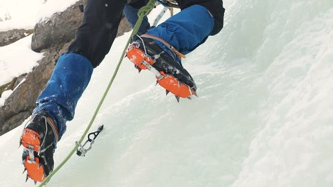 Ice Climbing Equipment:  Crampons. Climbers Climb Frozen Waterfall. Extreme Sport Alpinism. Crossing glaciers, snowfields and icefields, ascending snow slopes, and scaling ice-covered rock.