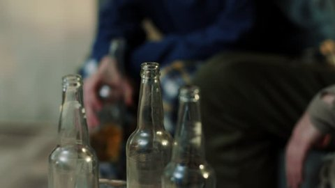 Close up a lot bottle drunk alcoholic man and woman with beer sit on sofa sleep talk in home drinker alcohol male belly adult alcoholism alone problem portrait depression stress cheers slow motion