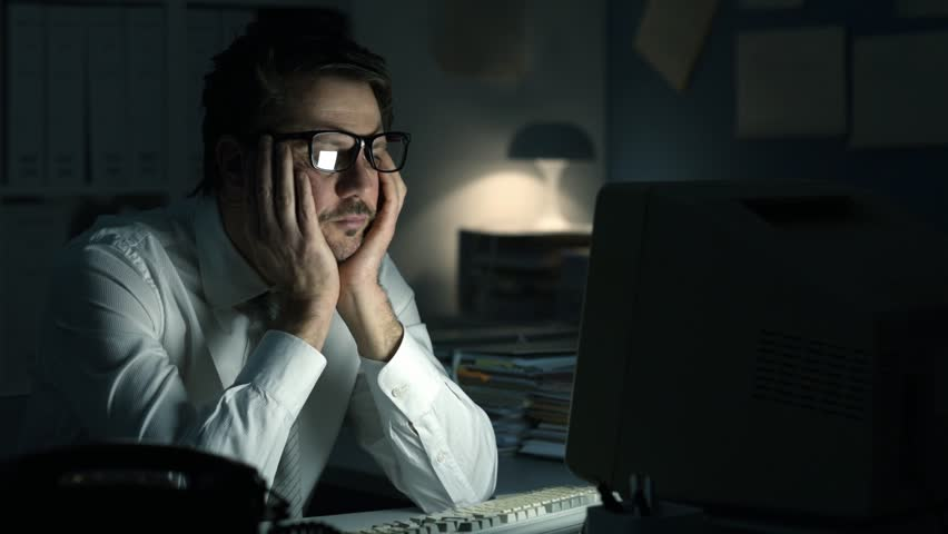 Tired frustrated business executive working late at night in the office, he is sitting at desk, staring at the computer screen and waiting   Shutterstock HD Video #1008714344
