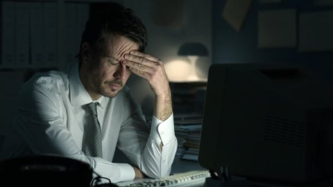 Tired frustrated business executive working late at night in the office, he is staring at the computer screen and receiving an error message