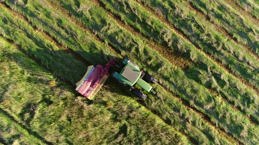 Aerial top down view of meadow with farmer in tractor cutting grass steady view following the agricultural vehicle used to mow the grass used when dried as animal fodder typical farm scene 4k quality