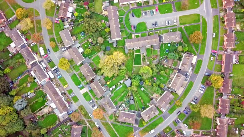 Aerial view of traditional housing estate in England. Looking straight down with a satellite image style, the houses look like a miniature village | Shutterstock HD Video #1008722384