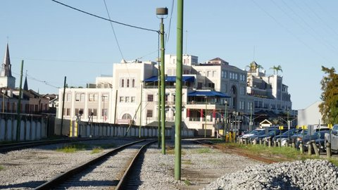 Old deserted urban railway track with parked cars to the side and a large commercial complex in the background
