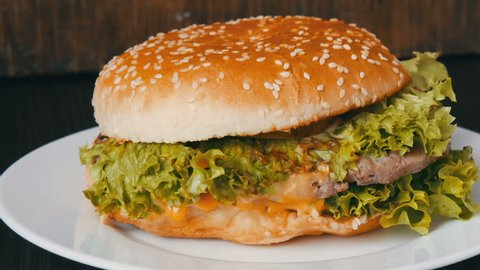 A large triple burger with lettuce leaves on a white plate. Hamburger on a stylish wooden background. Fast food