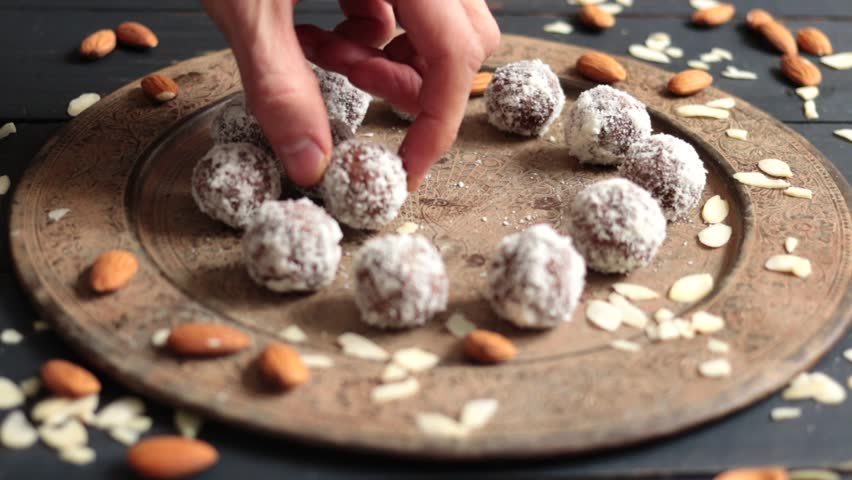 Hand puts raw vegan sweet chocolate energy balls on moroccan or Indian plate. Still life. With almonds, dates, cashew, coconut meat, cocoa powder. Closeup view. Vegetarian healthy food.
