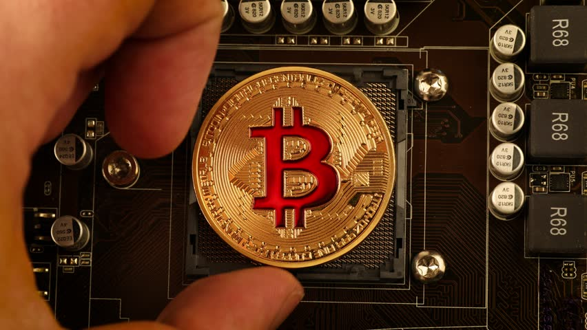 Gold Bit Coin BTC coins on the motherboard. Bitcoin is a worldwide cryptocurrency and digital payment system called the first decentralized digital currency. | Shutterstock HD Video #1008750254