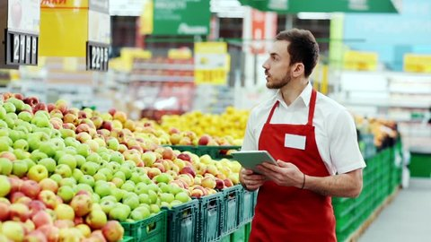Serious seller consultant using digital tablet in supermarket near fruit worker internet communication man holding connection job organic market store stand tablet pc shop touch business staff