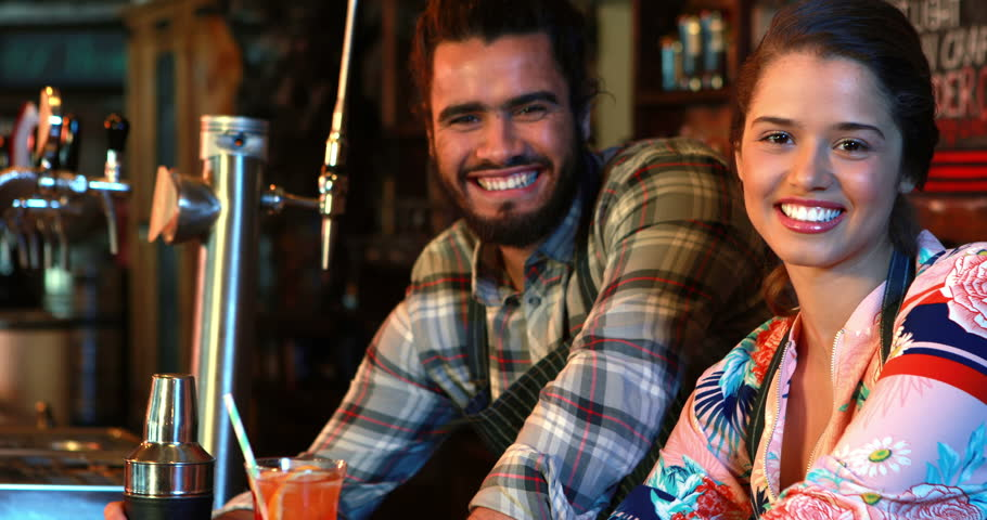 Portrait of smiling barmaid and barman with cocktail shaker and cocktail at bar counter in pub