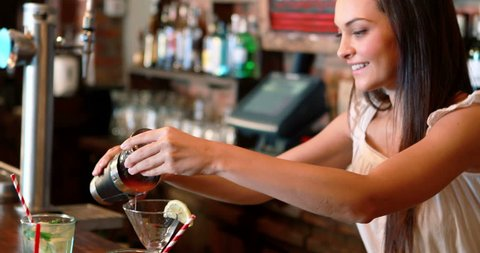 Barmaid pouring cocktail in glass at bar counter in pub