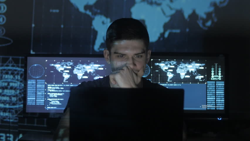 Hacker programmer in glasses is working on computer while blue binary code characters reflect on his face in cyber security center filled with display screens. | Shutterstock HD Video #1008776834
