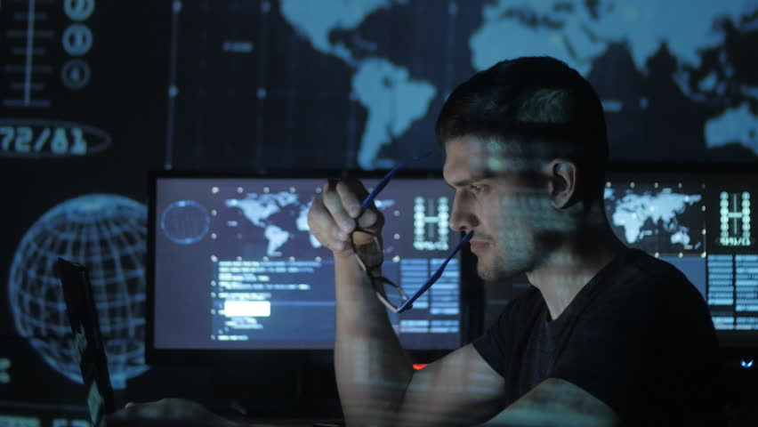 Portrait of a young programmer working at a computer in the data center filled with display screens   Shutterstock HD Video #1008776864