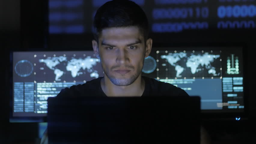 Male hacker programmer working at computer while blue code characters reflect on his face in cyber security center filled with display screens.   Shutterstock HD Video #1008780374