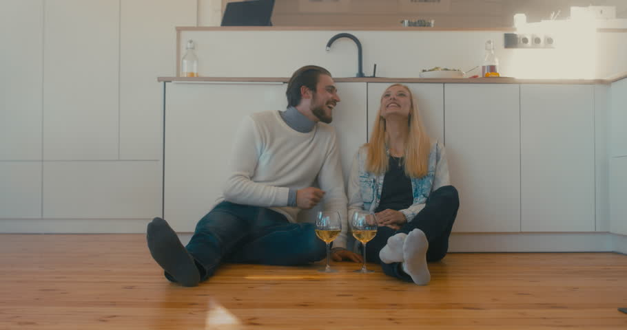 Young adult beautiful Caucasian couple celebrating something at home, drinking wine on the floor. 4K UHD   Shutterstock HD Video #1008781844