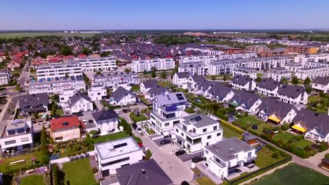 Aerial view over densely populated residential area in a green urban settlement, Cologne, Germany. Suburb with many detached house, semi-detached houses, apartment blocks and urban infrastructure.