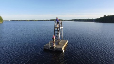 kids wave at drone from floating tower on lake
