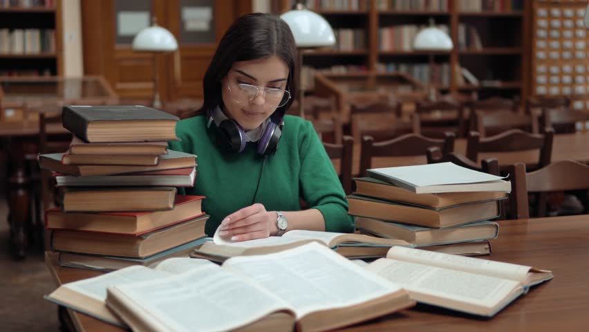 Bright student collecting information from different books, cute girl in green sweater and headphones around neck gathering data for the paper, indoor shot at brown library table