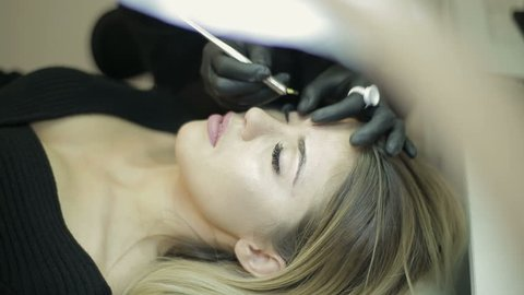 Beauty salon. Young woman gets facial beauty procedure.Microblading procedure
