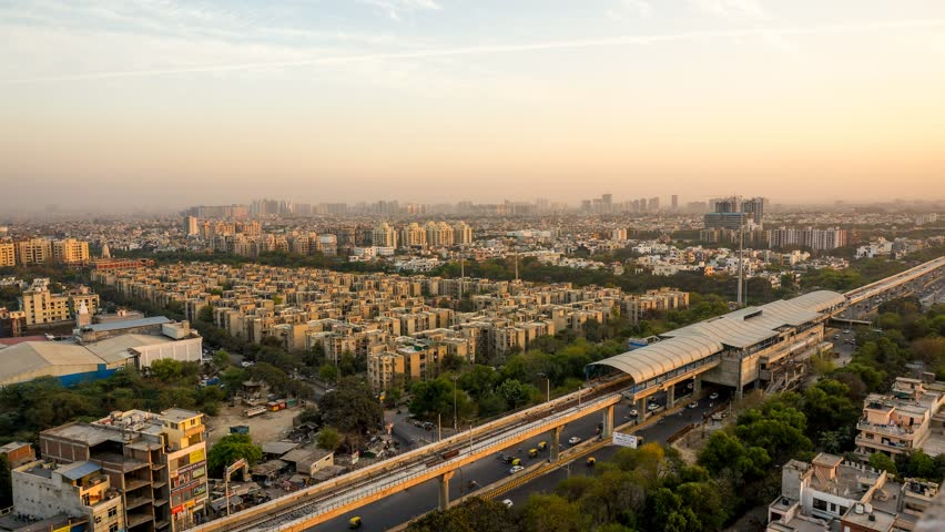 aerial timelapse shot of delhi noida gurgaon cityscape from evening to night shot over an hour with the sun setting, dusk light and the building lights coming on. Shows an incomplete metro station