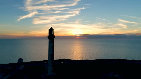Lighthouse on a sunset background in the sea in summer. Aerial flying of the drone past the lighthouse at sunset.