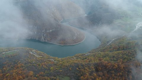 Mysterious drone flight through mist reveals autumn colored forest on mountains and river bend in Bosnia and Herzegovina, Southeastern Europe