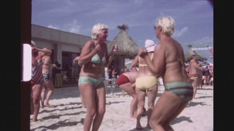 SPAIN, MALLORCA, JULY 1983. A Group Of Caucasian Tourists Participitating In A Chicken Dance Contest At A Beach Bar, Clapping, Dancing And Shaking.
