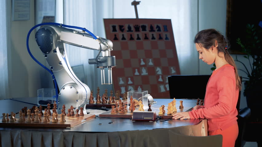 Smart scgool girl playing chess with a robotic arm, chess robot. Child genius concept.