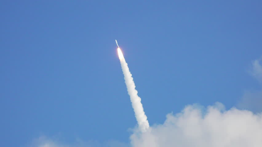 Nice shot of space rocket lifting-off into blue sky as it passes through clouds with exhaust flames and lots of smoke. 120 fps slow motion.