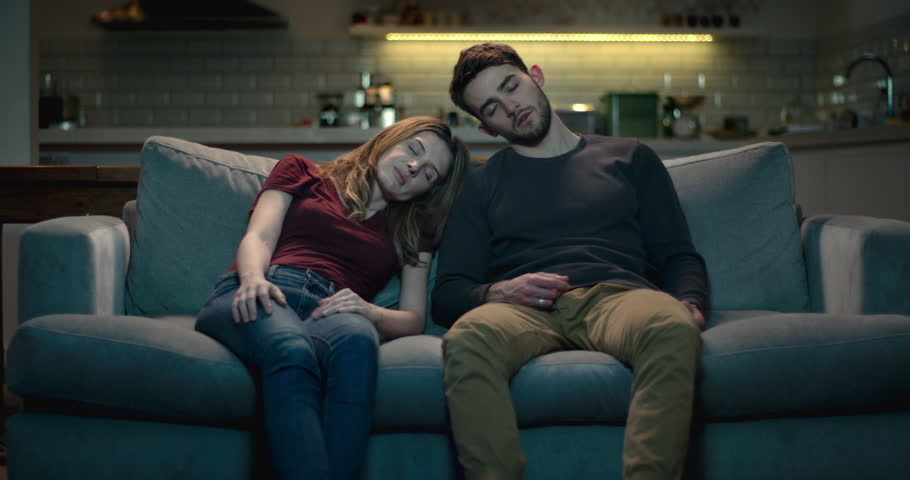 Tired and exhausted young couple asleep on the sofa after a long day. | Shutterstock HD Video #1008855284