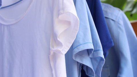 White T-shirt color among blue hanging on clothes line outside the home, housewife's working