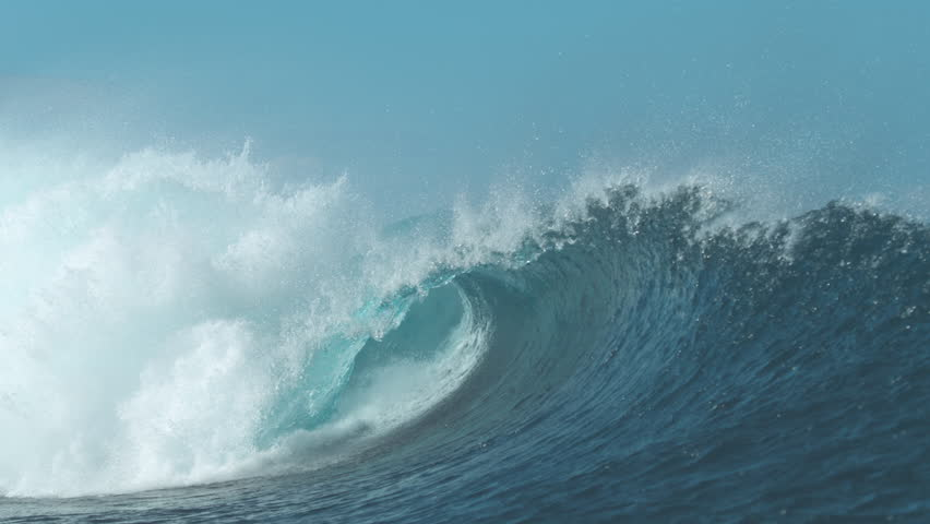 SLOW MOTION, CLOSE UP: Stunning barrel wave shines brightly in the pretty summer sunlight. Huge tropical wave coming from the endless ocean rushes towards empty beach. Breathtaking natural wonder.