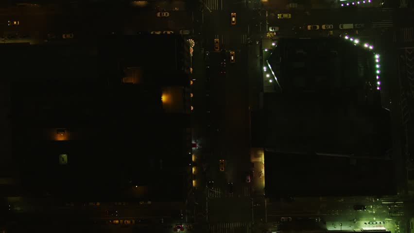 Aerial wide shot of yellow taxis riding through the streets in New York in the night | Shutterstock HD Video #1008903374