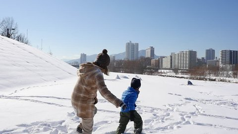 Asian mother and her son playing snow together in the park , sapporo japan slow motion