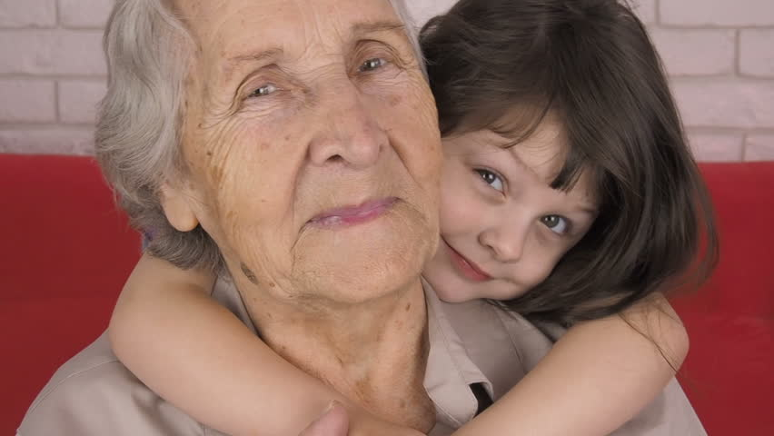A child is hugging her grandmother. Portrait of an elderly and a child.