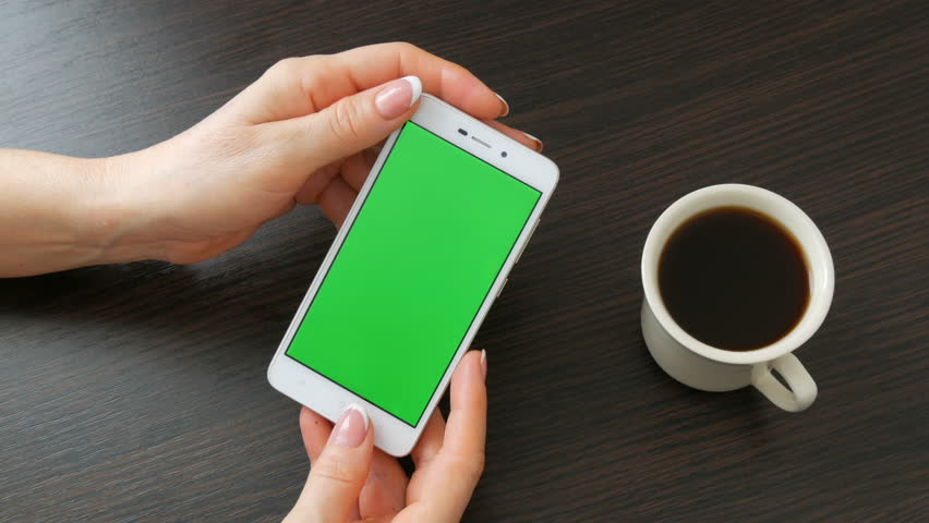 Female hands with beautiful French manicure take white smartphone with Green Screen near white cup of coffee. Using Smartphone,Holding Smartphone with Green Screen on a stylish black wooden table #1008951194