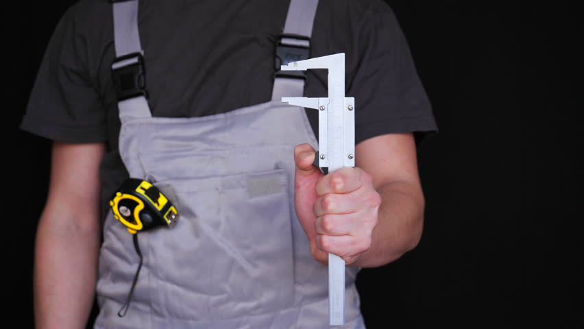 The master, builder or repairman holds a caliper in his hand, in a special suit, a yellow tape measure of metrics, a black background.